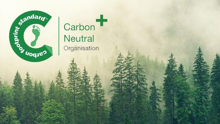 Carbon Neutral Plus logo against a forest landscape