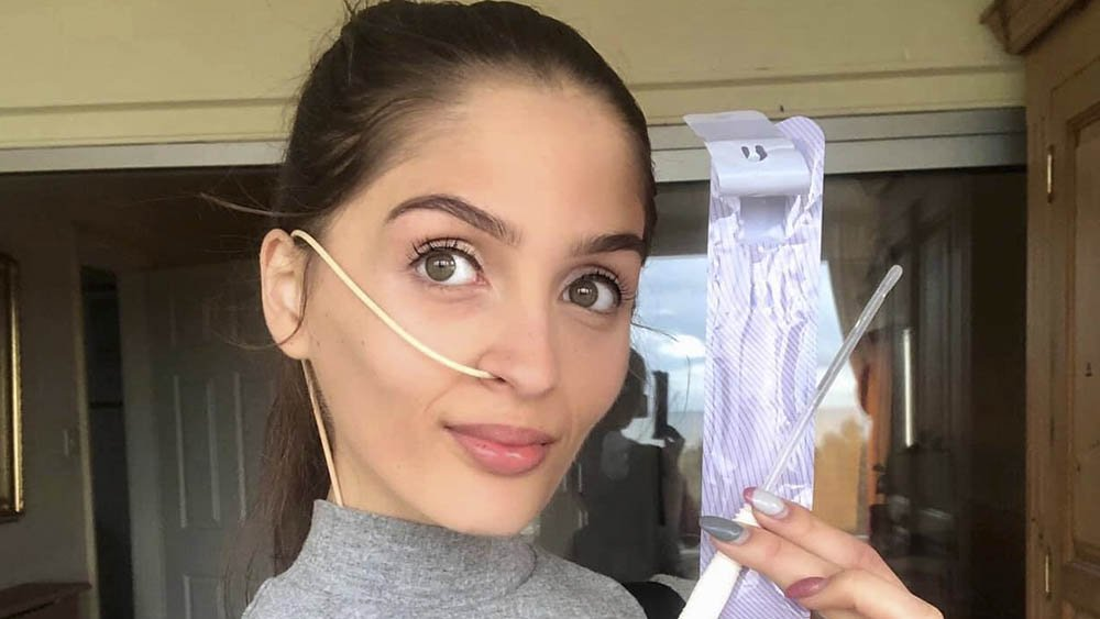 Evie Toombes confidently holding a catheter for managing her bladder and supporting her independence